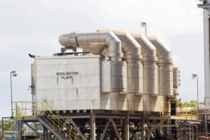 Closeup view of desalination plant.  Square factory with four fat round vent pipes rising up over the back of the building and over the roof, shaped like four fingers with finger tips over the top facing left.