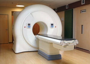 large cylinder MRI machine with donut hole; long 7 ft table in front of the donut hole, slides though the donut hole; donut hole large enough for a person lying down to slide through on the table